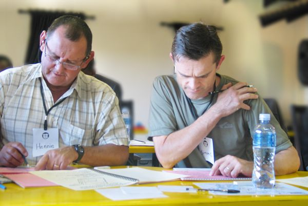 A mine manager and contractor work on establishing a common understanding of Project Management challenges during an intensive workshop in Midrand, Gauteng.